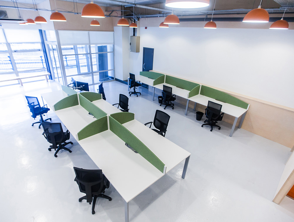 Working office area with White desks and green separator. Black chairs